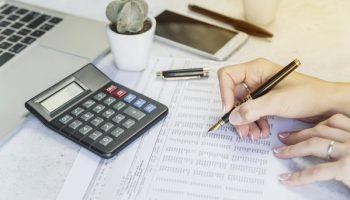 mao-segurando-caneta-checando-papel-em-uma-mesa