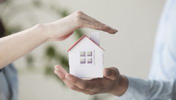 mãos segurando miniatura de casa