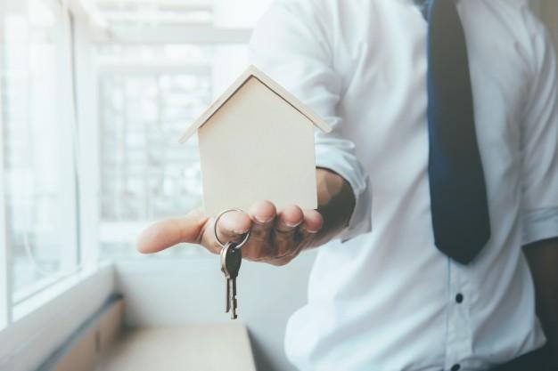 pessoa segurando miniatura de casa e chaves