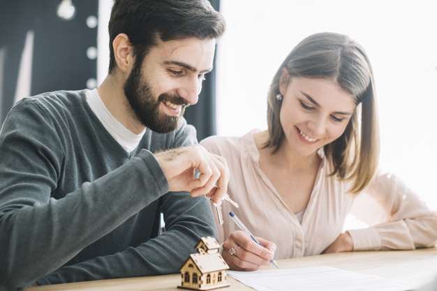 casal sorrindo assinando papeis