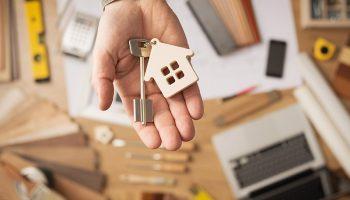mão masculina segurando chave e miniatura de casa