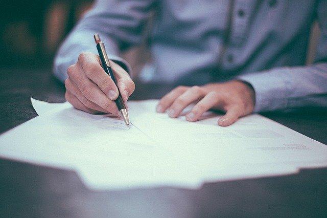 homem escrevendo em documento
